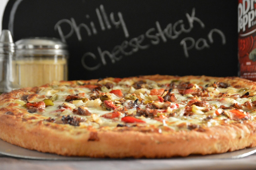 PHILLY CHEESESTEAK PAN: your choice of A-1, marinara, garlic-butter and ranch dressing, mozzarella, Philly Steak, roasted peppers, roasted onions, topped with provolone cheese.