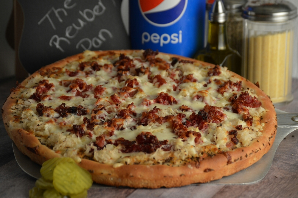 THE REUBEN PAN: Homemade Russian dressing, swiss and provolone cheese, pastrami and corned beef brisket, sauerkraut, seasoned with caraway seeds.  (ONLY AVAILABLE IN PAN CRUST)
