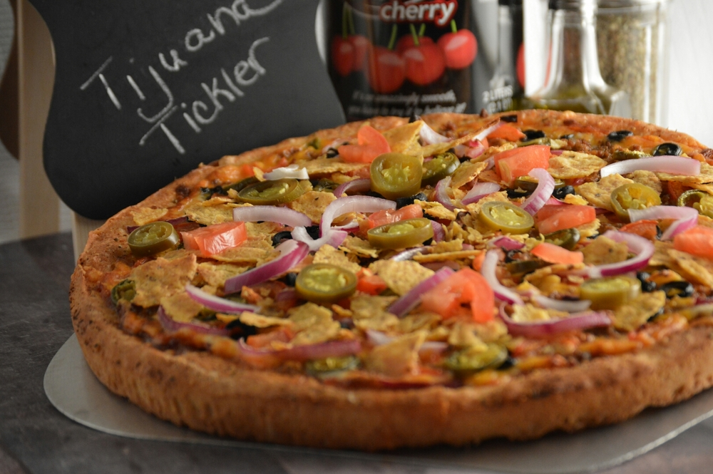 TIJUANA TICKLER PAN: Salsa, provolone cheese, cheddar cheese, taco beef, onions, roma tomatoes, black olives, jalapenos and topped with nacho chips.   (ONLY AVAILABLE IN PAN CRUST)