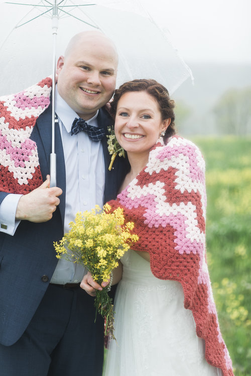Bride Annie said Chippy's knitted-afghans saved their wedding, offering cozy accommodations for guests during a summer storm. By her husband Mike's side, Annie's blue eyes shine bright despite gray skies. Photos by  Nicole DuMond's Photography .