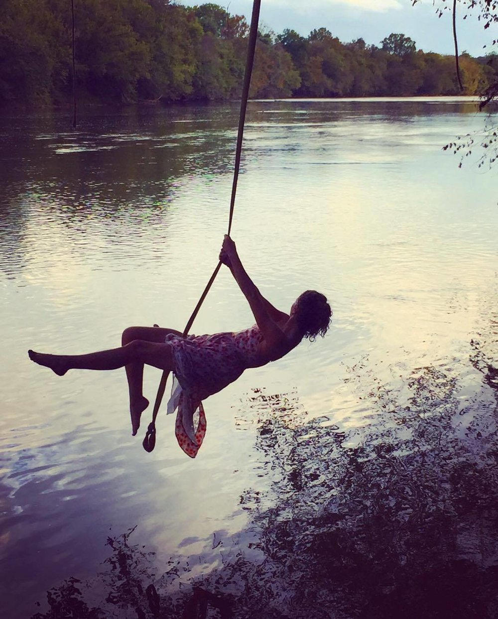 Michaela Coleman on a rope swing over lake