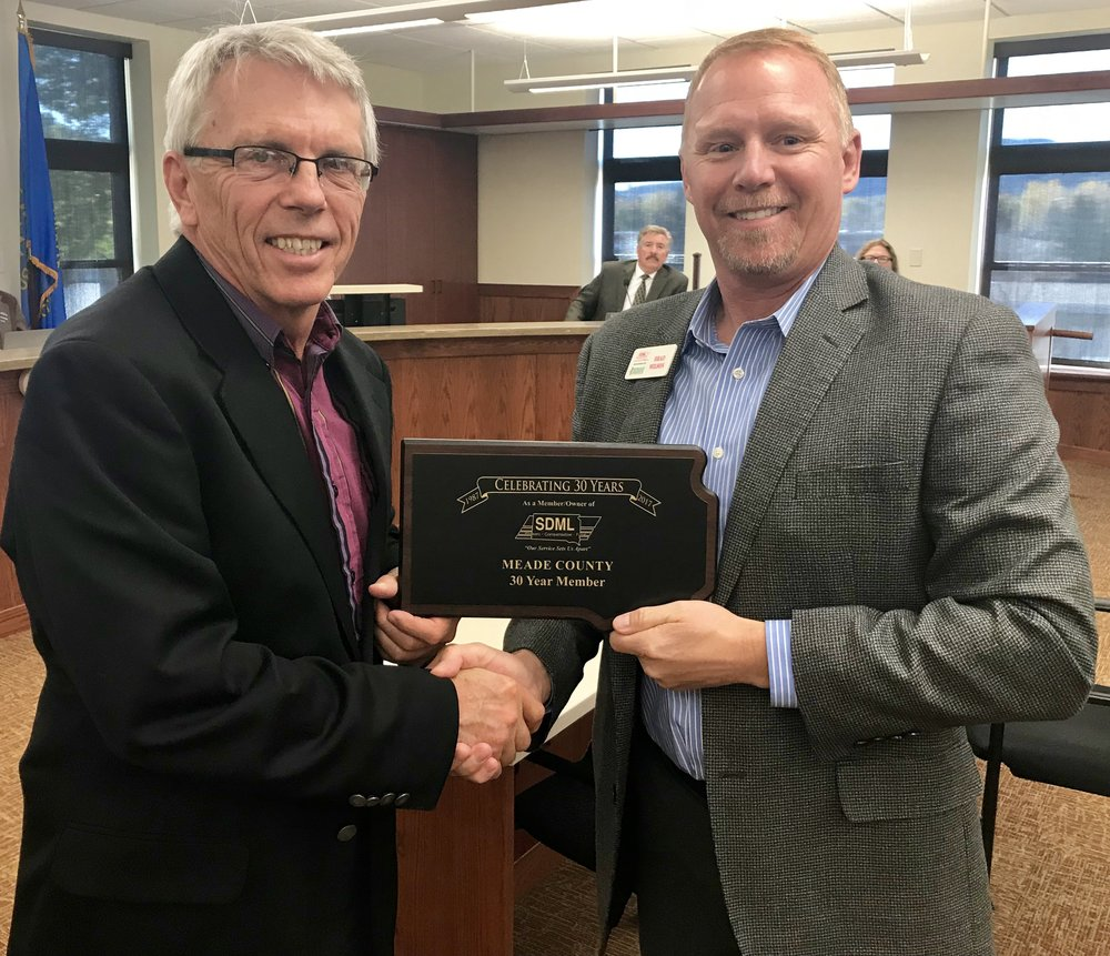 County Commission Chairman Galen Niederwerder is pictured above accepting a plaque from SDML Workers' Compensation Fund Administrator, Brad Wilson.