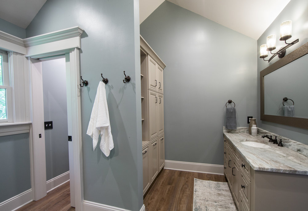 The opening to the left has a pocket door that opens to the private water closet.