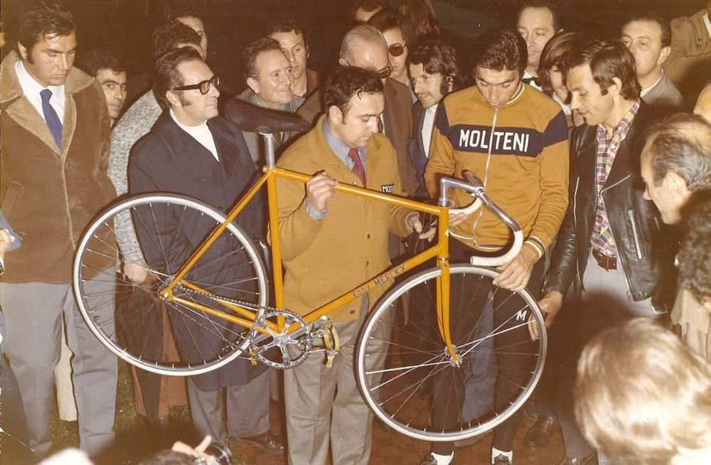 In the picture, taken at the   Vigorelli Velodrome in Milan   in October 1972 (before leaving for Mexico City), note   Ernesto Colnago holding the record bike (a mechanical in suits!)  , at his side Eddy Merckx and Ole Ritter, with black leather jacket.