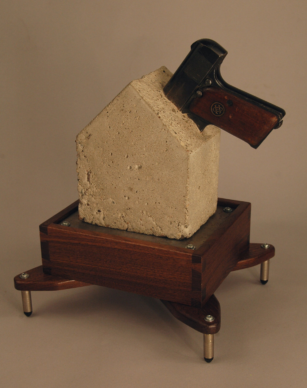 "My contribution to the project:   Safe, Effective, Stylish Device for Handgun Storage in the Home ; 2016; wood, concrete, steel, bullet casings, disabled handgun; 18""h x 17""w x 14""d"
