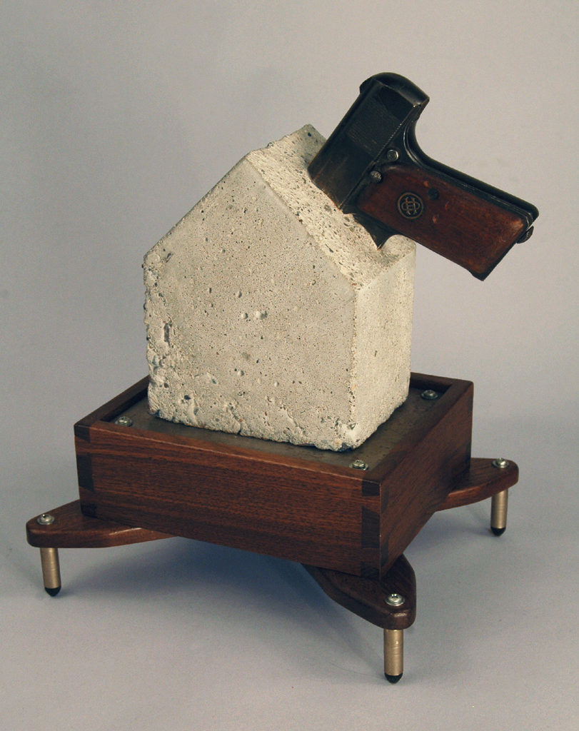 "11.         Title:  Safe, Stylish Object for Handgun                 Storage in the Home               Media: Wood, steel, concrete, brass,              disabled handgun                          Dimensions: 16""h x 14""w x 12""d"