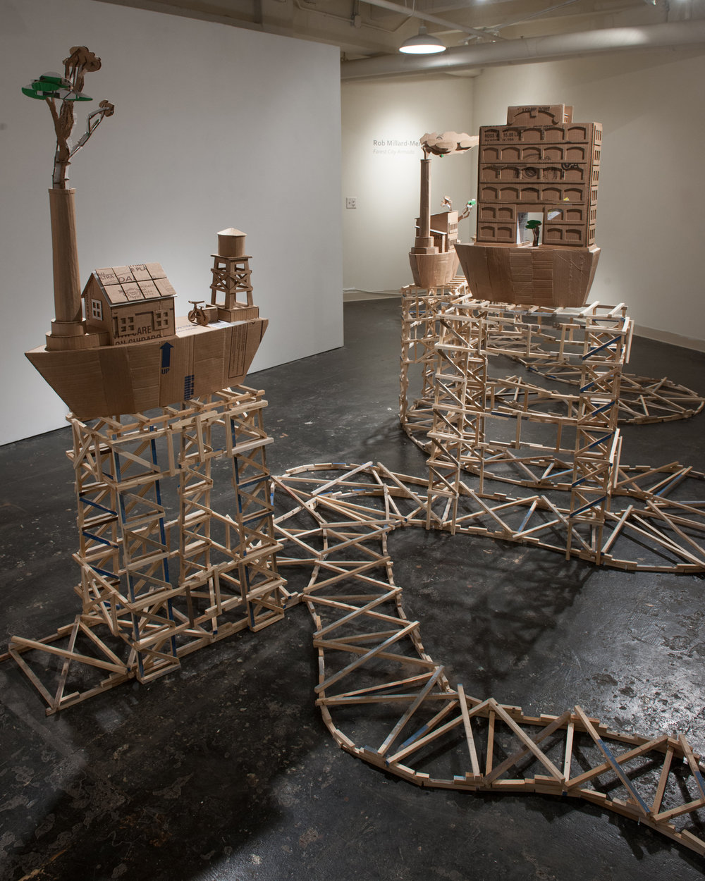 "16.        Title:  Forest City Armada               Media: Recycled cardboard, wood              Dimensions: 72""h x 120""w x 150""d"