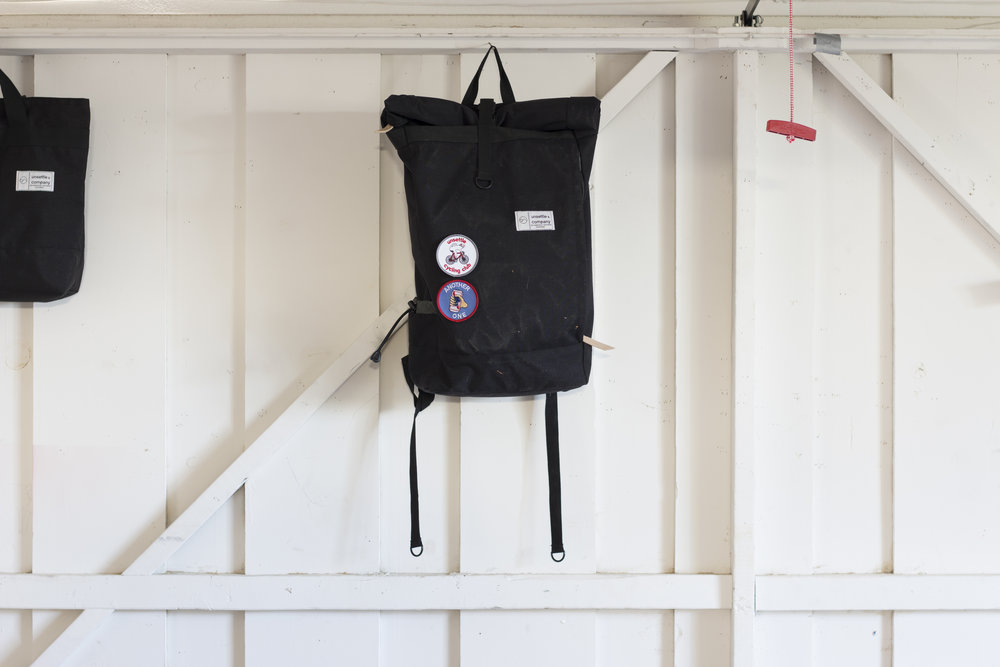 unsettle-co-lifestyle-blog-behind-the-scenes-shipping-day-space-black-commuter-rolltop-backpack-white-wall