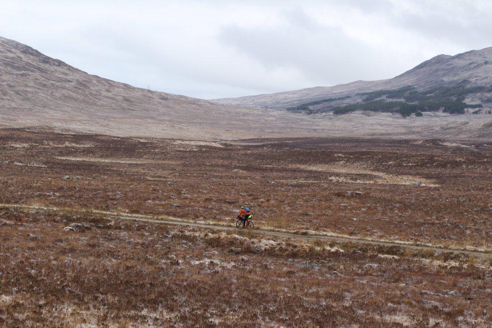 cyclist biking through the plain field