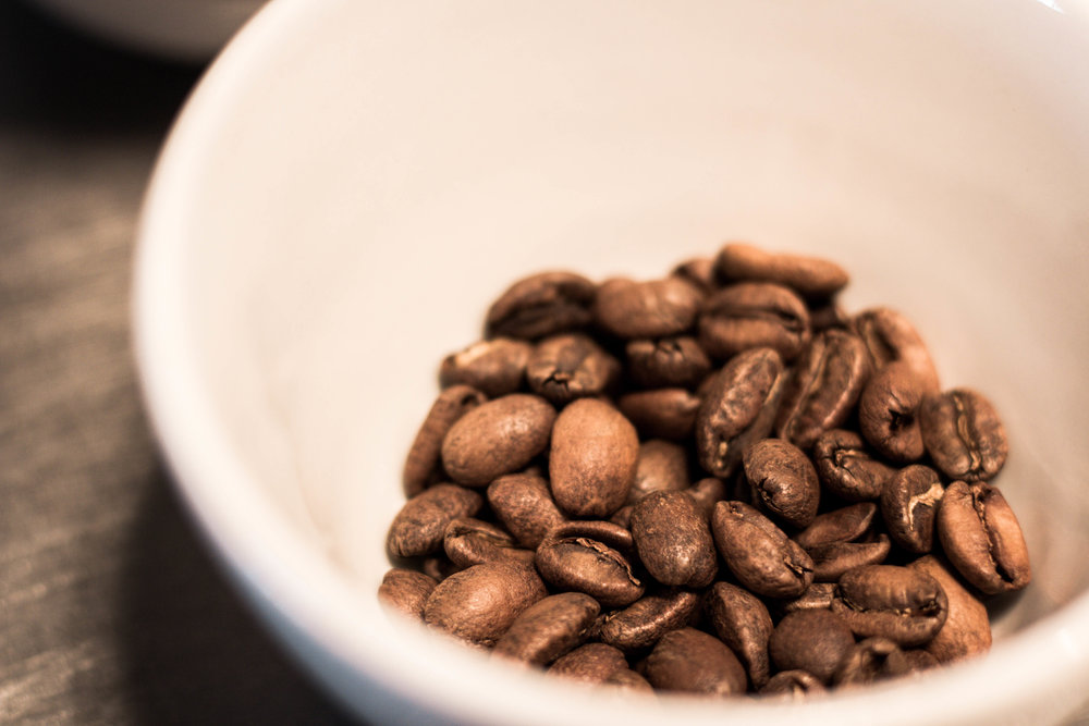 close up of roasted whole coffee beans in a cup
