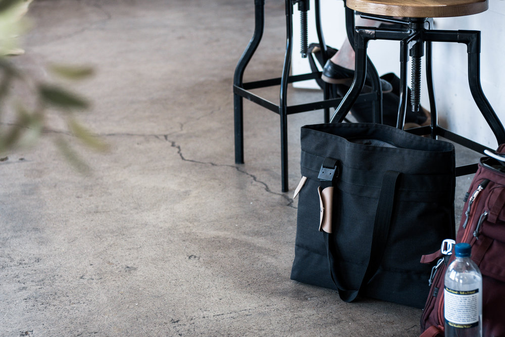 the commuter tote bag lifestyle shot at communal coffee