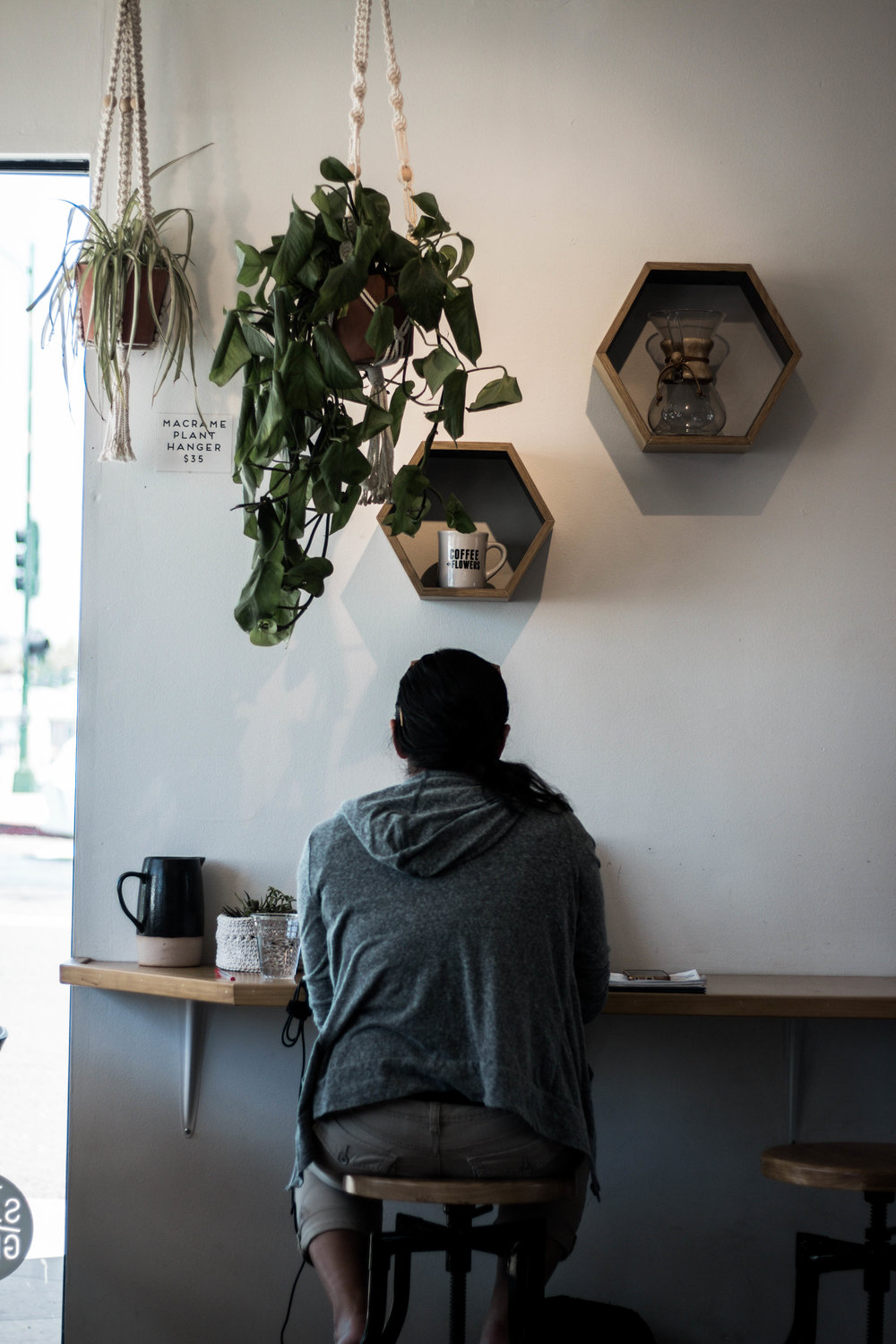man sitting at coffee shop communal coffee with hung ceiling planters