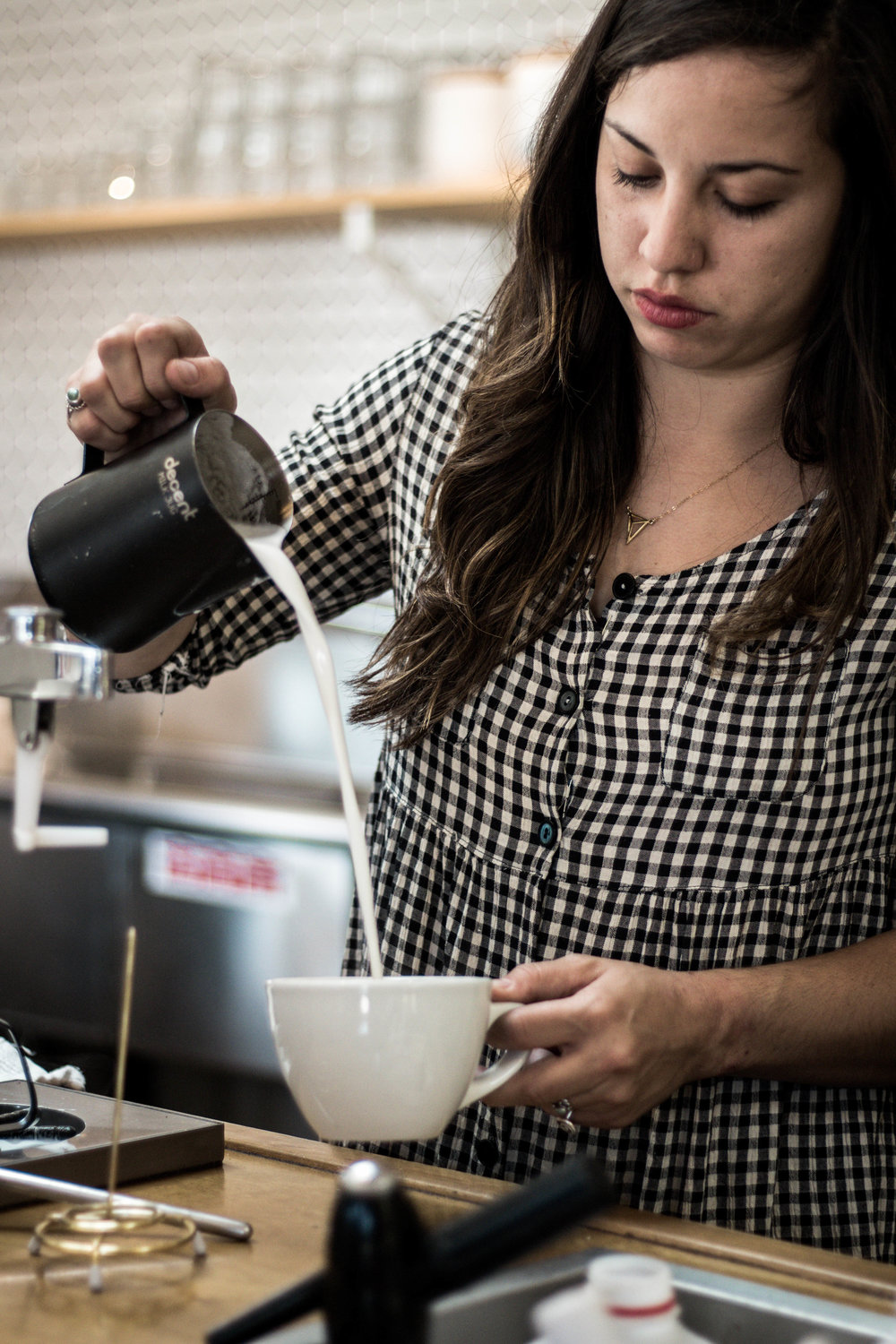 coffee barista pouring milk to prepare a latte at communal coffee