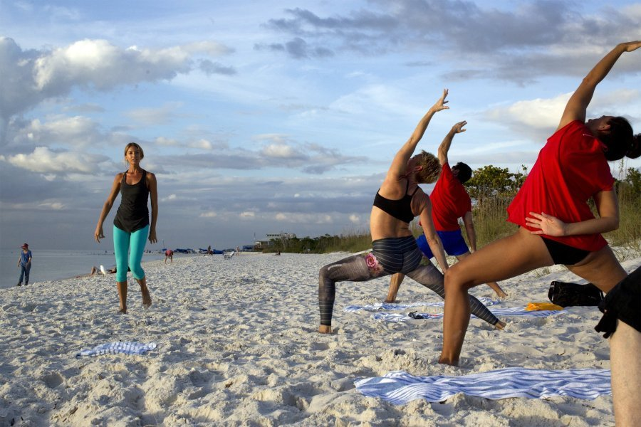Wendy Campbell leads a beach yoga class, organized by the Naples Grande hotel at Clam Pass on Dec. 5, 2014. The sunset lessons are organized by the hotel's spa. (Carolina Hidalgo/Naples Daily News Staff)