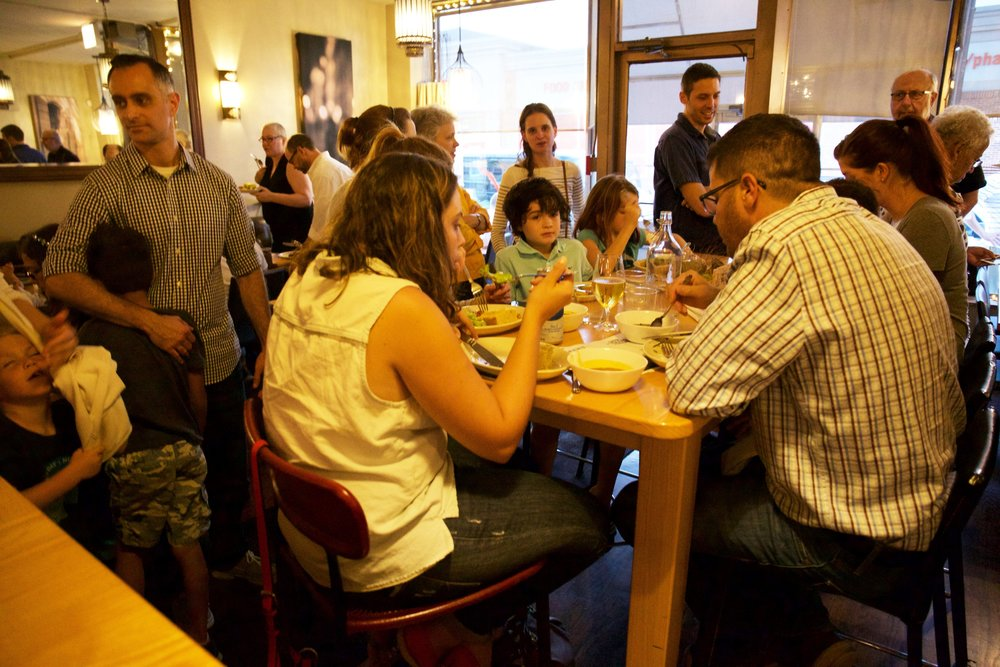 Full dining room at Autre Monde! Over 120 people attended our first Family Dinner.