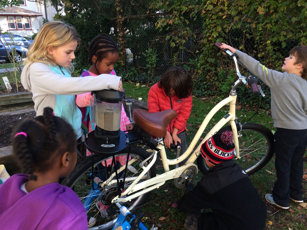 "Students in the Good Food Experience after school program at Longfellow Elementary make ""Vampire Proof Garlic Hummus"" in the Blender Bike after planting garlic beds."
