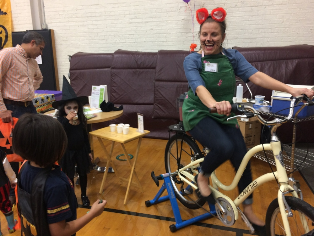 Gina Milkovich,  of Sugar Beet Food Co-op, captured kids' attention and passes out smoothies at the River Forest Community Center's Halloween Party. Blender Bike smoothies easily compete with candy- they are so good!