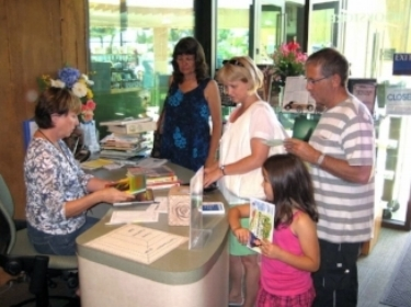 Friends of the Encinitas Library Bookstore cashier's desk where customers are purchasing books.