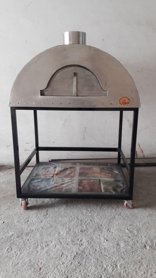 Black mobile wood oven with steel shelf for storage of wood.