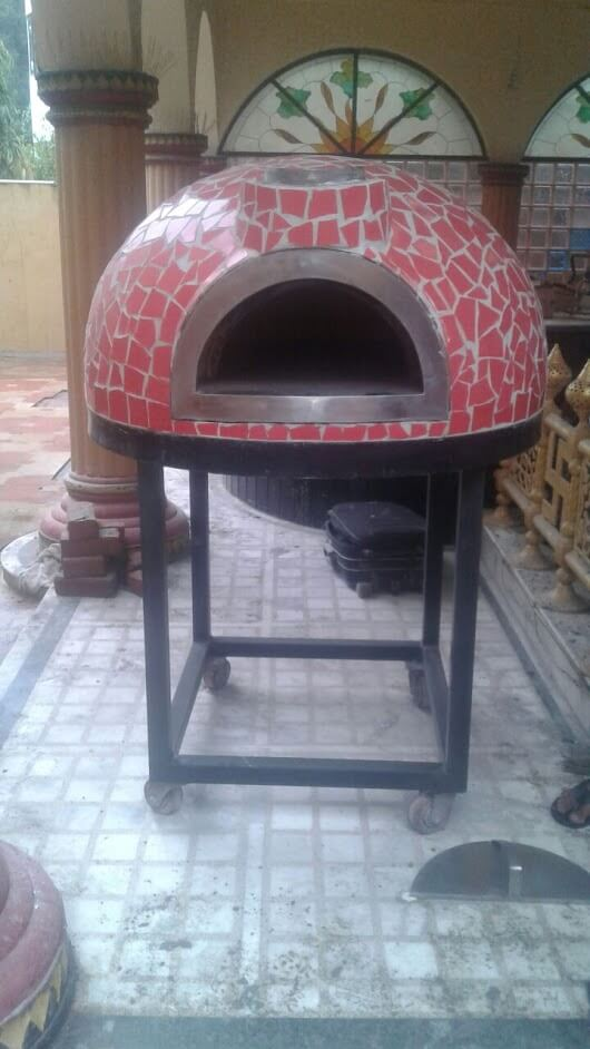 Small brick oven on a trolley. The oven has red broken tile mosaic finishing.