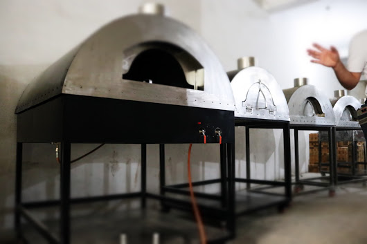 Black mobile metal oven in front. Three metal ovens in the background.