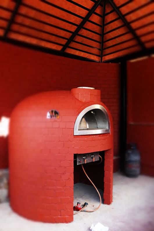 A fixed wood fired oven with painted red mosaic.