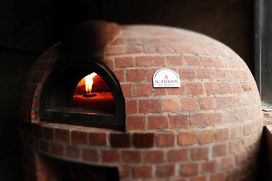 A dome shaped brick oven with red bricks finishing. There is a flame from the gas burner inside the oven.