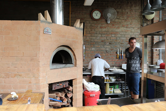 A straight brick oven with red bricks finishing. Marco and a chef is making pizza.