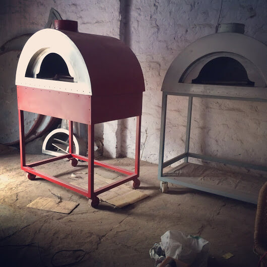 A red metal wood fired oven in the front. Behind this one there is a grey metal oven.