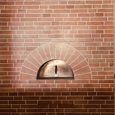 A red brick wall with a oven behind.