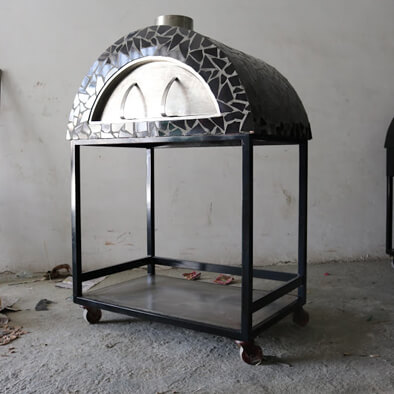 A metal wood fired oven on a black torlley on wheels. The shell of the oven is covered with black broken tile mosaic.