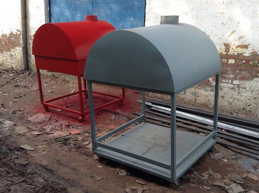 Two wood fired ovens. The one in the front is grey. The one in the back is red.