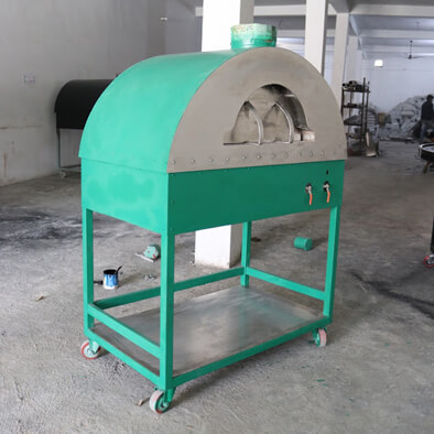 Green wood fired oven with a stanless steel shelf underneath.