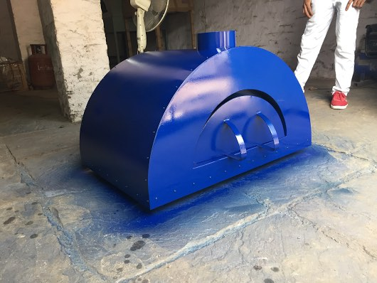 A blue newly painted small wood fired oven.