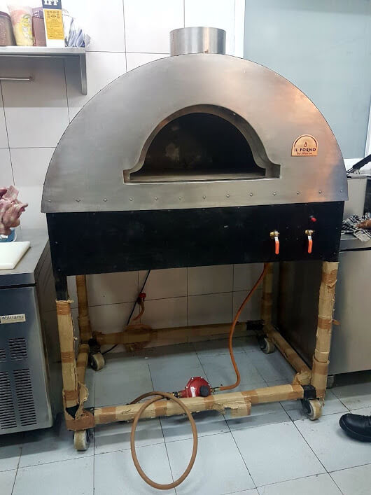 A black wood fired oven on a trolley.