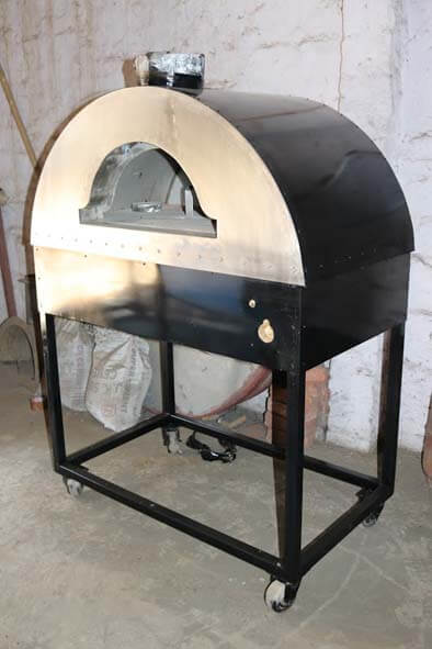 A black wood fired oven on wheels with a space for gas burner system.