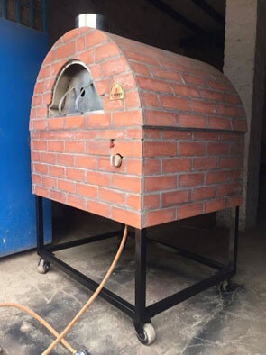A mobile metal oven that is covered with red brick veneers.
