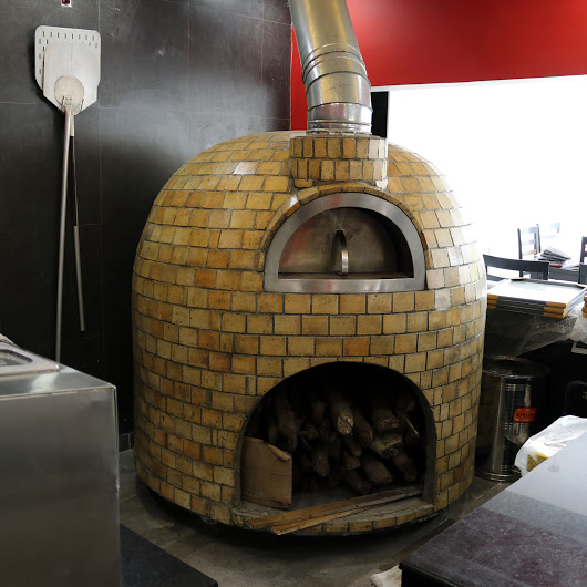 A semi-mobile brick oven with fire brick finishing all the way down to the floor.