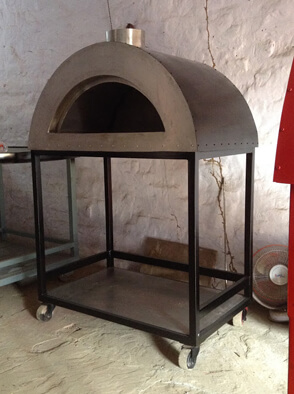 Black mobile oven with a shelf for storing of wood.