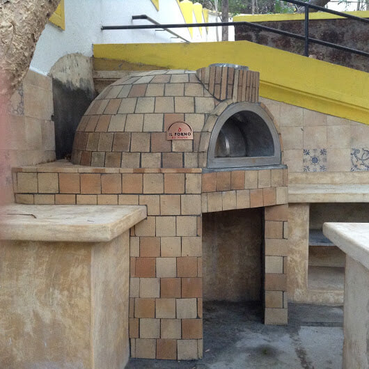 A outdoor kitchen with a fixed brick oven with fire brick finishing.