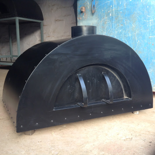 A black wood fired oven in front of a blue door.