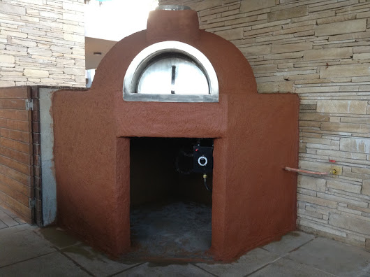 A fixed brick oven with red clay finishing in front of a stone wall.