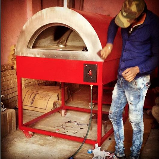 A labour polishing a red wood and gas fired oven.