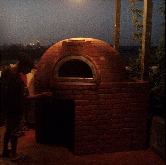 A dome shaped fixed oven with red brick finishing in dawn.