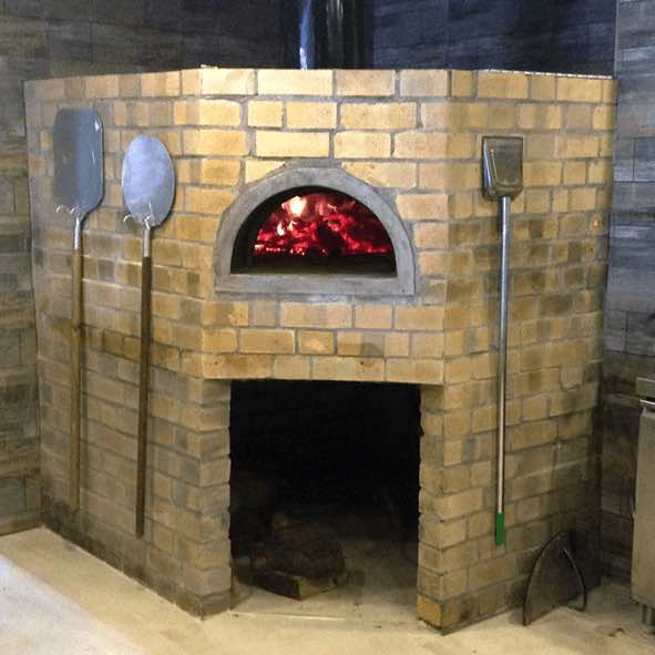 A fixed brick oven with fire brick finishing. On both sides of the oven mouth there are pizza peels hanging.