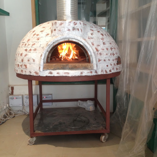 A wood fired oven on a red painted trolley. The oven finishing is partly coloured with white paint.
