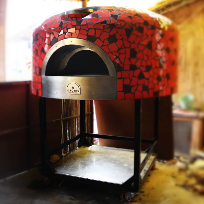 semi-mobile wood fired oven with a steel shelf for wood. The oven has broken tile mosaic finishing in red and black.