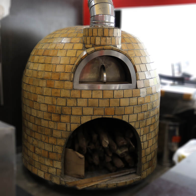 A semi-Mobile brick wood fired oven with fire bricks finishing. The oven has a opening with a shelf for storage of wood.