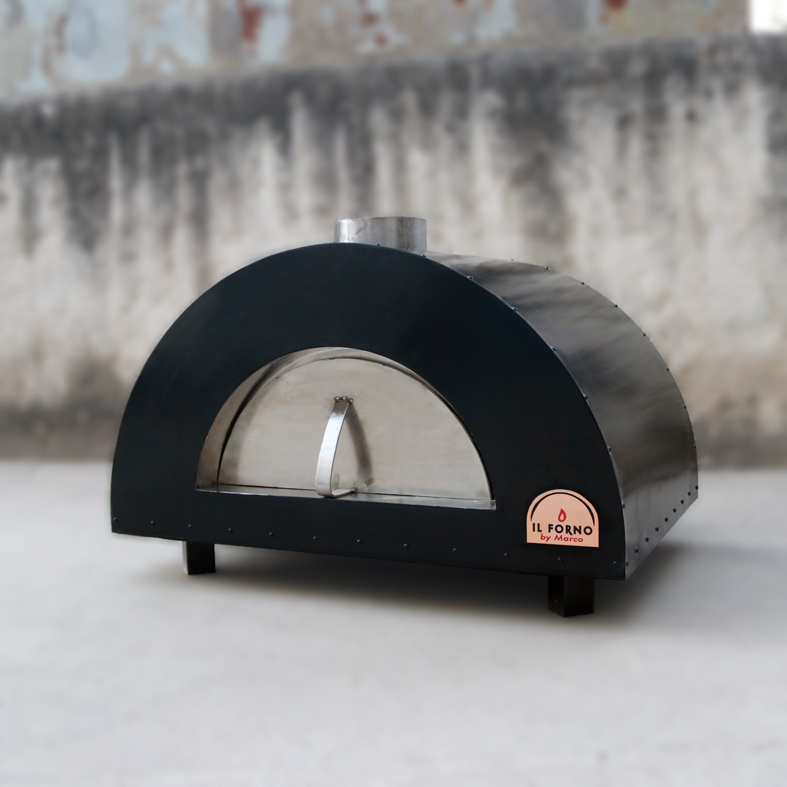 A small wood fired oven in metal standing on the floow. It has black epozy paint finishing. The Il Forno By Marco logo is visible to the right.