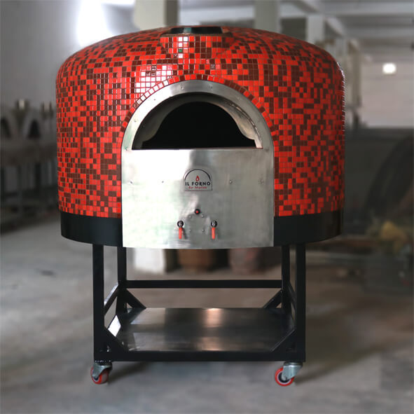 A semi-mobile brick oven with red and black mosaic tile finsihing. The oven is on a black trolley on wheels that has a shelf for storage of wood.